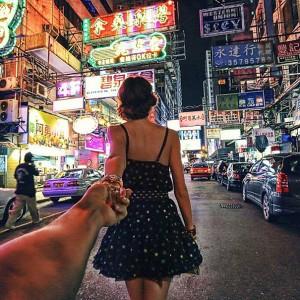girl leading boy through city street